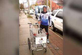 Joe Roberts behind the shopping cart he is pushing from coast-to-coast to raise awareness of youth homelessness in Canada.