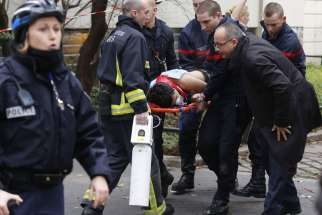 "Firefighters carry a victim on a stretcher at the scene of a shooting at the Paris offices of Charlie Hebdo, a satirical newspaper, Jan. 7. Pope Francis condemned the killings of at least 12 people at the offices and denounced all ""physical and moral"" ob stacles to the peaceful coexistence of nations, religions and cultures."