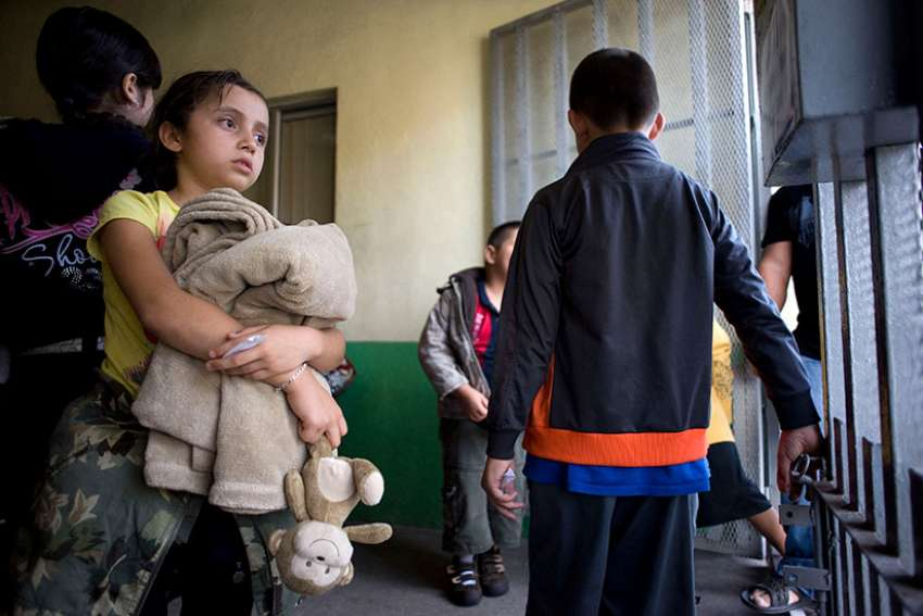 A young girl holds her belongings as she waits with a group of Mexicans preparing to leave the Casa del Migrante shelter June 8 in Tijuana, Mexico.