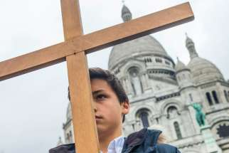 A boy stands with cross outside Sacre Coeur basilica in Paris April 3. Catholic churches in France have been placed under police protection and urged to take extra security measures against possible Islamist attacks before the Aug. 15 feast of the Assumption.