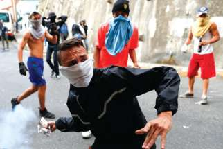 A demonstrator throws back a tear gas canister while clashing with the Venezuelan National Guard Jan. 21 during a protest close to one of their outposts in Caracas.