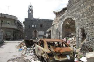 A destroyed car is seen outside a school in Homs, Syria. Two car bombs exploded near the school Oct. 1, killing at least 47 school children. On a visit to Canada, Jesuit Father Ziad Hilal, working with Jesuit Refugee Service in Syria, urged caution and c alled for renewed efforts to find peace.