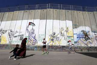 Participants run past the controversial Israeli separation barrier during the annual Right to Movement Palestine Marathon in Bethlehem, West Bank, April 1.