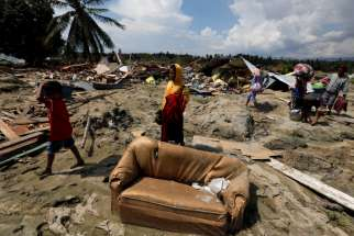 Villagers carry their belongings as they walk through mud near the ruins of houses after an earthquake hit Indonesia's Sulawesi island.