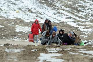 A group of migrants from Syria, Iraq and Afghanistan, on their way to seek asylum in Germany or Austria, walk Jan. 24 along the frozen route from the border between Serbia and Macedonia to a temporary camp for migrants.