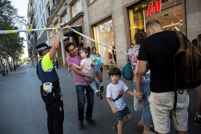 A police officer helps evacuate people after a van crashed into pedestrians in the Las Ramblas district of Barcelona, Spain, Aug. 17. Terrorists killed at least 12 and injured more than 50 others.