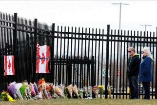 A man and woman stand before a makeshift memorial at the Royal Canadian Mounted Police headquarters in Dartmouth, Nova Scotia, April 20, 2020. The previous day, a shooter went on a 12-hour rampage that left at least 19 people dead.