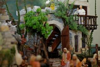 A tiny statue of Pope Francis is seen waving from a balcony on a miniature Nativity scene depicting a Middle Eastern village set inside the Holy See press office Dec. 19 at the Vatican.