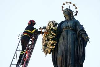 A firefighter places a wreath on a tall statue of Mary overlooking the Spanish Steps in Rome Dec. 8, the feast of the Immaculate Conception. Rome's firefighters have observed the tradition every year since 1857.