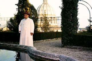 Blessed John XXIII is pictured in the Vatican Gardens with the dome of St. Peter's Basilica in the background in this undated photo.