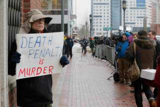 "A man holds a sign reading ""Death penalty is murder"" March 4 outside the trial of accused Boston Marathon bomber Dzhokhar Tsarnaev in Boston. Four nationally circulated Catholic publications called for abolishing the death penalty in the United States in a jointly published editorial March 5."