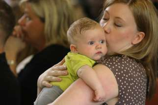 A mother kisses her 3-month-old son during Mass in Huntingtown, Md., May 3. An Italian priest is offering more than $2,000 to Catholic couples who have three or more children under certain conditions.