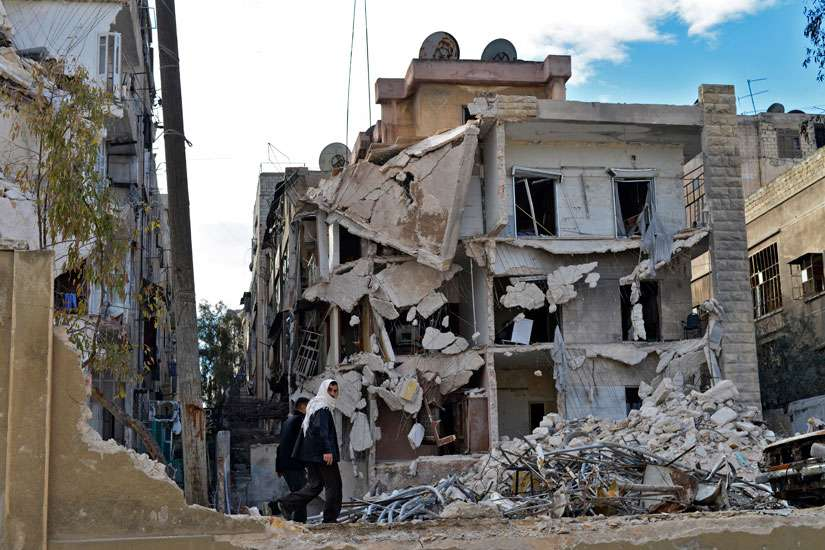 Residents walk past a destroyed building in 2014 after airstrikes in Aleppo, Syria. Pope Francis says the war-torn country needs a political solution not a military one.