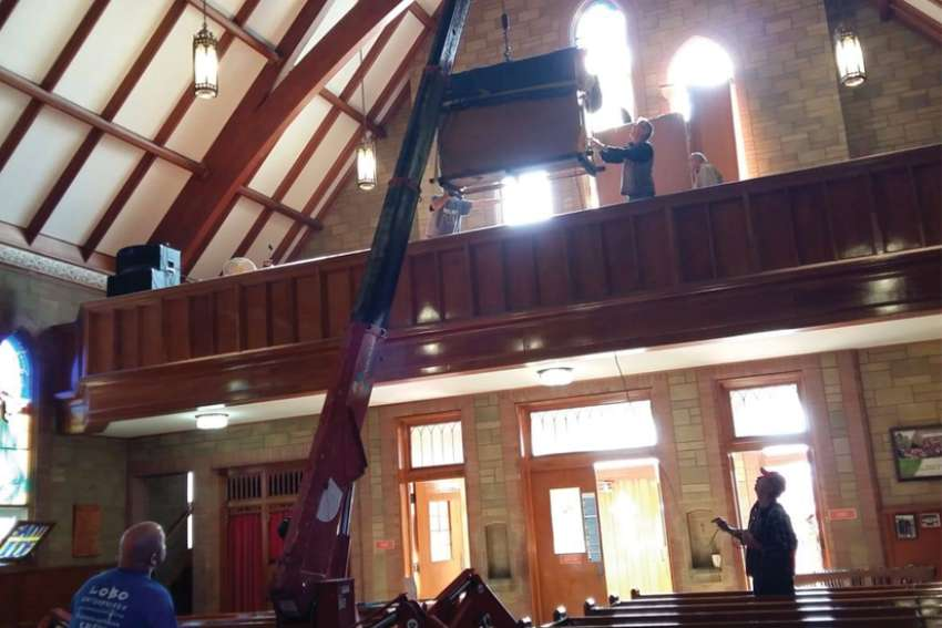 A spider crane lifts the 770-pound electic organ into its new home.