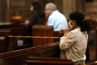A woman prays during Mass at the Catholic Church of the Immaculate Conception in London July 4, 2020, during the COVID-19 pandemic. Catholic leaders in England are appealing to the government to reverse its decision to ban public Mass during a second national lockdown.