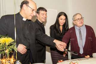 Scripture scholar Msgr. Bob Nusca, left, historian Fr. Seamus Hogan, theologian Josephine Lombardi and homiletics expert Deacon Peter Lovrick cut into a cake at a celebration of their recent publications. Lovrick pubished A Practical Guide to Catholic Preaching in 2016, Lombardi brought out Experts in Humanity in 2016, Hogan's Extraordinary Ordinaries arrived this year, and Nusca's Contemplating the Faces of Jesus in the Book of Revelation hit bookshelves this year.