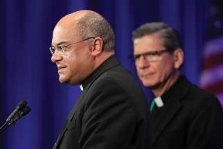 Bishop Shelton J. Fabre of Houma-Thibodaux, La., speaks Nov. 13 at the fall general assembly of the U.S. Conference of Catholic Bishops in Baltimore. Looking on is Archbishop Gustavo Garcia-Siller of San Antonio.