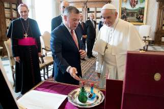 Pope Francis exchanges gifts with Jordan's King Abdullah II during a private meeting Dec. 19 at the Vatican. At left is Archbishop Georg Ganswein, prefect of the papal household.