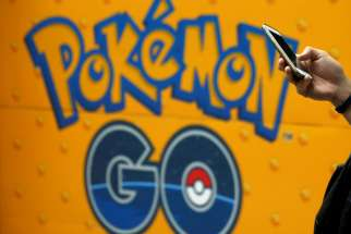 "A man uses a mobile phone in front of an advertisement board bearing the image of ""Pokemon Go"" at an electronic shop in Tokyo on July 27, 2016."