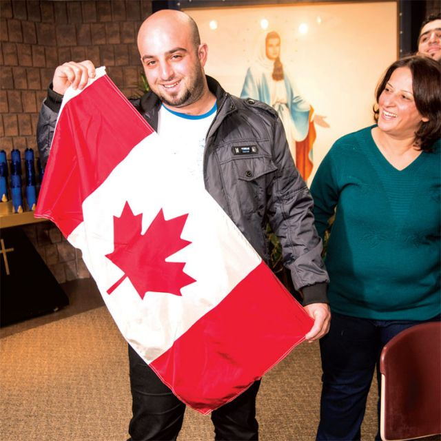 Fady Meera proudly waves the Canadian flag as his mother Landa and two of his siblings, brother Rani and sister Vahlia, look on.