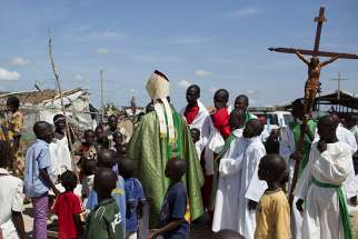 Cardinal Dieudonne Nzapalainga of Bangui, Central African Republic, greets youths after celebrating Mass for internally displaced people in Bangui in this 2015 file photo. Catholic bishops in the Central African Republic have distanced themselves from a group that is promising to defend the church and avenge the deaths of priests.