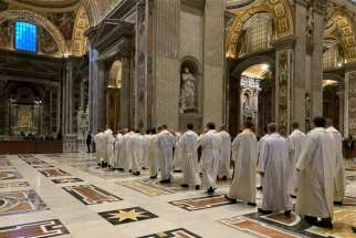 Priests in St. Peter's Basilica process to the altar where St. John Paul II is buried at the Vatican in this Feb. 13, 2020, photo. Dozens of priests concelebrate an early morning Mass at the tomb every Thursday.