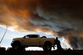 People wait at a roadblock May 7 as smoke rises from wildfires near Fort McMurray, Alberta. Pope Francis has added his name to the list of people offering condolences to those affected by the massive forest fire that has led to the evacuation of Fort McMurray.