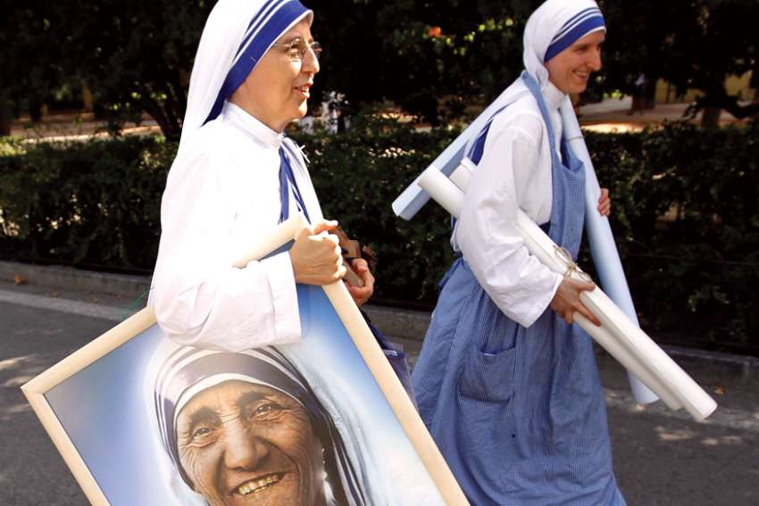 In this 2011 file photo, a member of the Missionaries of Charity carries a portrait of St. Teresa of Kolkata in Madrid's Buen Retiro park.