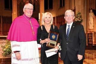 Teresa Susi is presented with her Award for Distinguished Service by Hamilton Bishop Douglas Crosby and Patrick Daly, chair of the Hamilton-Wentworth Catholic District School Board.