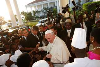 Pope Francis greets people as he arrives with Ugandan President Yoweri Museveni at the State House in Entebbe, Uganda, Nov. 27.