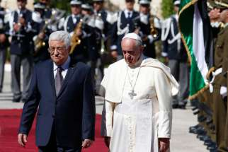 Pope Francis reviews the honour guard with Palestinian President Mahmoud Abbas during an arrival ceremony at the presidential palace in Bethlehem, West Bank, May 25, 2014.