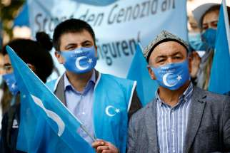 A man holds a Uyghur flag at a rally in Berlin during the visit of China's Foreign Minister Wang Yi Sept. 1, 2020. The religious persecution exercised by China and North Korea, restrictions on religious freedom in dozens of countries and the continuing threat of violence at the hands of religious fundamentalists belonging to a variety of faiths all have worsened since 2018, said Aid to the Church in Need, a papal foundation and Catholic charity.