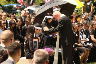 Msgr. Richard Paperini comforts Myhanh Best, wife of Ricky Best, who was killed on a Portland, Ore., commuter train May 26 while defending two girls from an anti-Muslim racist attack. The ceremony was held June 5 at Willamette National Cemetery in Portland, following a funeral Mass for Ricky Best at Christ the King Church in Milwaukie, Ore.