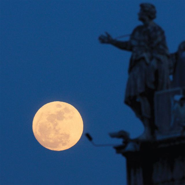 A full moon is juxtaposed with statues of saints on the colonnade in St. Peter's Square at the Vatican. A formula has been devised using a full moon to pinpoint the date of Easter, but still we don't have a firm date that Roman Catholics and Orthodox can agree upon.