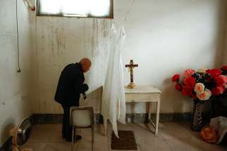 A retired bishop waits to hear confession from members of the congregation before Mass Dec. 23, 2016, at an unofficial Catholic church in Youtong village, Hebei Province, China.