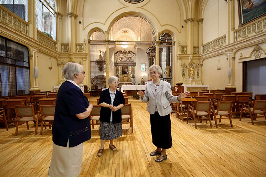 Ursuline Sister Cecile Dionne speaks to Sister Pauline Duchesne and Sister Celine Bergeron inside Quebec City's Ursuline monastery chapel June 1. In October, the majority of the 50 sisters who live in the monastery, founded by St. Mary of the Incarnation, will head to the borough of Beauport, where a new home for the elderly awaits them.