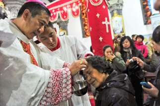 Chinese Catholic priests baptize new believers during a 2013 Easter Vigil in a church in Shenyang, China. The Vatican put out a statement, amidst rumours of new bishops secretly ordinated in China, that ordination of bishops without the papal mandate is a serioius violation of church law.