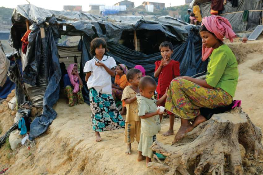 A Rohingya family sits outside their tent at a refugee camp in Cox's Bazar, Bangladesh.