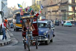 A man rides a bicycle taxi with several national flags on it along a street in late March in Havana. Pope Francis will visit Cuba in September before his trip to the United States.