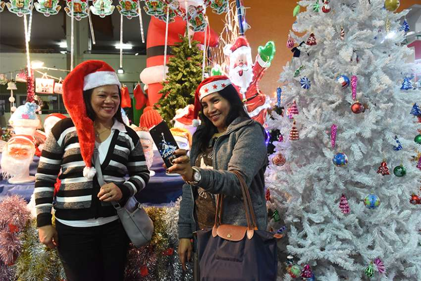 Angeline Fernando and Vangie Lapada, foreign workers from the Philippines, take a selfie wearing Santa hats at the Christmas market in the central bus station in Tel Aviv, Israel, Dec. 9. The market offers an opportunity for foreigners to buy decorations for Christmas in the Jewish state.