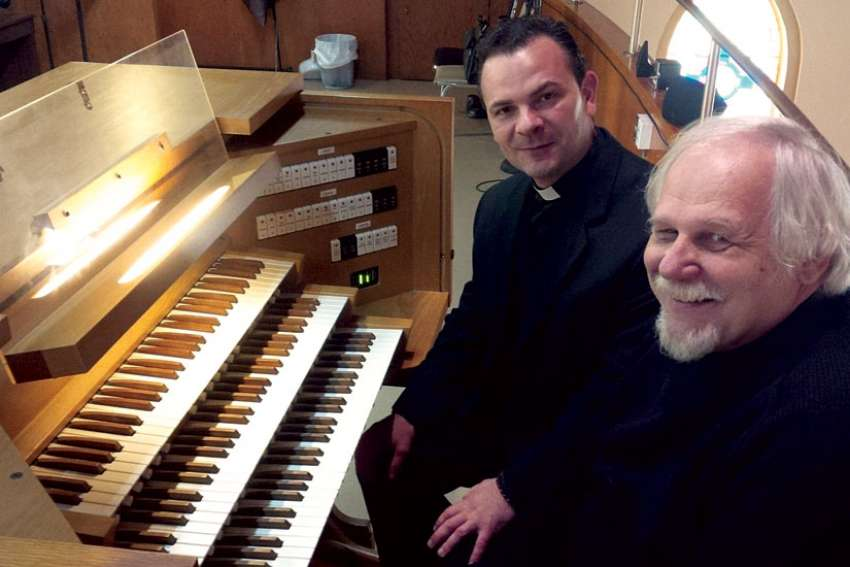 Fr. Donatello Iocco, left, with St. Ambrose Church organist Gregory Furmanczyk at the Allen AP-35 organ a donor gave to the parish.