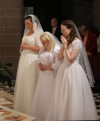 Karen Ervin, Theresa Jordan and Laurie Malashanko pause in prayer before the altar at Detroit's Cathedral of the Most Blessed Sacrament in 2017. They were consecrated into the Catholic Church's order of virgins.