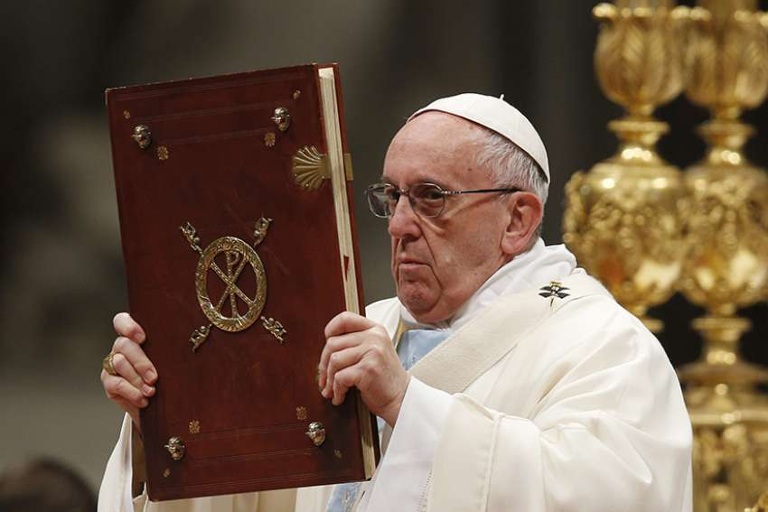 Pope Francis raises the Book of the Gospels during a Mass marking the feast of Mary, Mother of God, in St. Peter's Basilica at the Vatican Jan. 1.