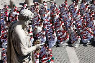 Priests sit below the statue of St. Peter as Pope Francis celebrates Mass marking the feast of Sts. Peter and Paul in St. Peter's Square at the Vatican June 29. In an Aug. 20 letter to all Catholics, the pope blamed clericalism for helping to support and perpetuate sexual abuse committed by clergy.
