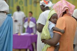 "A mother holds her child during Mass in 2014 in Juba, South Sudan. Western governments are ""spitting in the face"" of African democracy by trying to impose legal abortion against the wishes of most of the people in such countries, a Catholic Nigerian campaigner said."