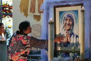 A woman reaches to touch a painting of Mother Teresa at Christo Rei parish in Mississauga, Ont., Sept. 4. The parish celebrated a Mass in the new saint's honour on the day she was named St. Teresa of Calcutta. The Mass was celebrated by Cardinal Luis Antonio Tagle of the Philippines.