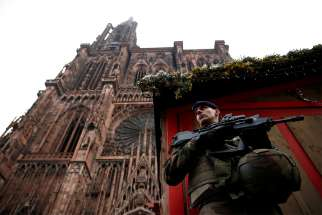 A French soldier stands guard near a closed wooden barrack shop at the traditional Christkindelsmaerik (Christ Child market) in front of the Cathedral of Our Lady of Strasbourg Dec.12, the day after a shooting. At least two people were killed while one person was left brain dead and at least a dozen others were injured after a gunman attacked the market Dec. 11, authorities said.