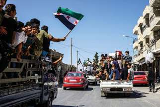 People carry Syrian revolution flags and placards Sept. 14 during protests in Kafr Nabl, Syria.