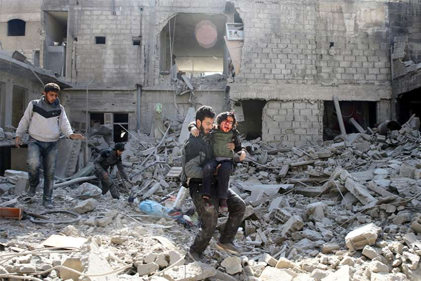 A man carries an injured boy amid destroyed buildings Feb. 21 in rebel-held Eastern Ghouta, a suburb of Damascus, Syria.