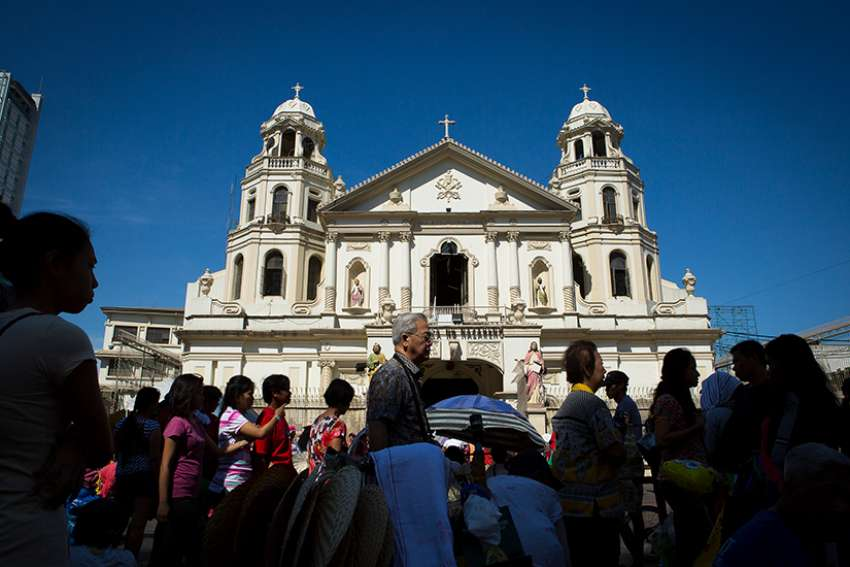People stroll in front of the Minor Basilica of the Black Nazarene in Manila, Philippines, in this 2014 file photo.